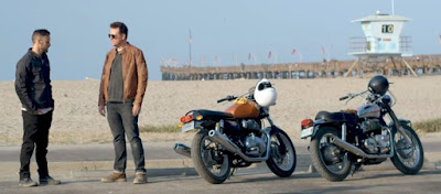 Two men and two motorcycles on the beach near a pier.