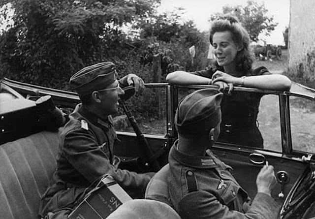 German soldiers and a French girl engage in a conversations