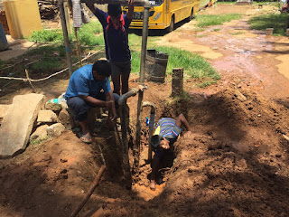 Arun working hard digging dirt to find a leaking pipe
