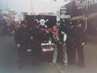 A color photograph of John Belushi and five men in police uniforms posing in front of a vehicle in the middle of a highly decorated street.