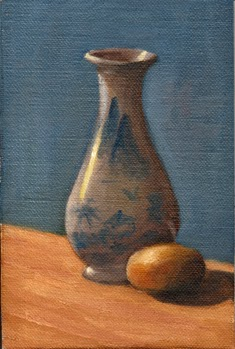 Oil painting of a blue and white miniature onion-shaped vase beside a sandy-coloured pebble with a blue background.