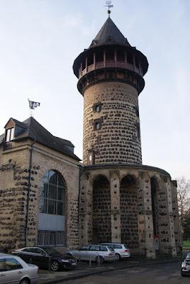 Ein hoher, runder und gemauerter Turm mit einem Spitzdach und einem roten Rundbalkon. Der Anbau links hat eine große Glasfassade.