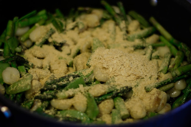 The nutritional yeast in the pan with the vegetables and gnocchi.