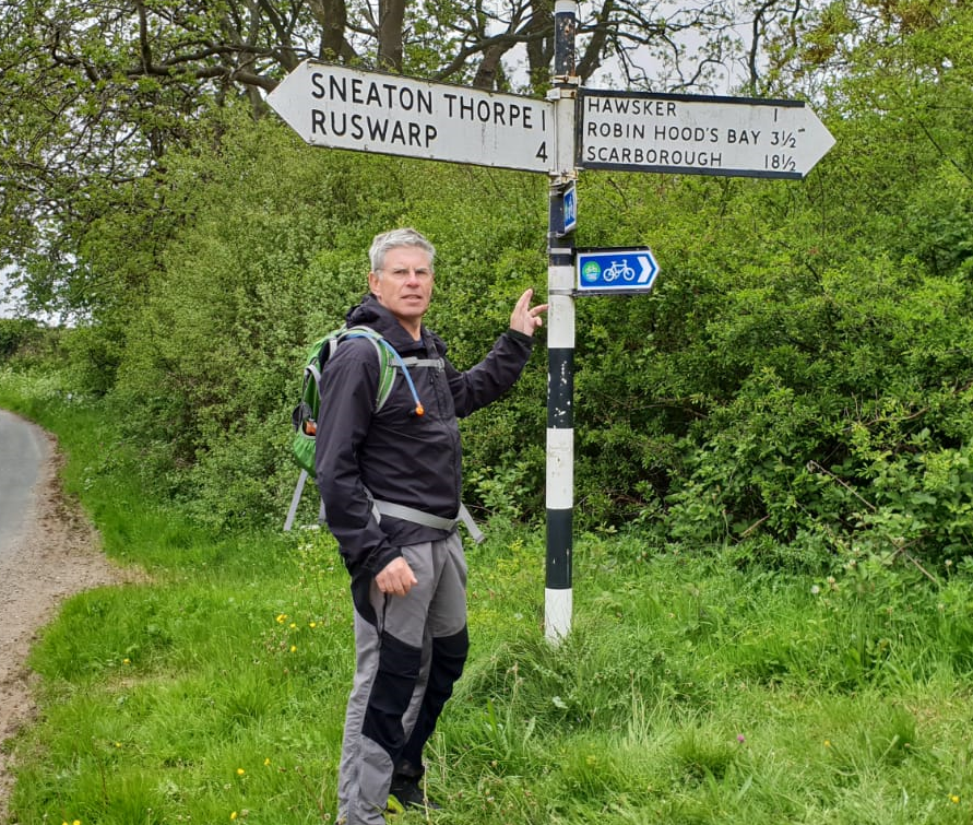 Road sign showing a walker the mileage to Robin Hood's Bay on the final day of the Coast to Coast wak