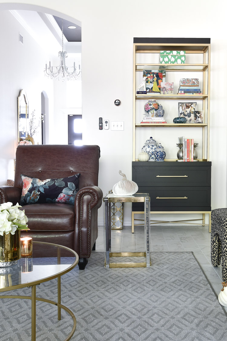 A white living room with a black and gold bookcase with eclectic and chinoiserie decor paired with a brown leather recliner.