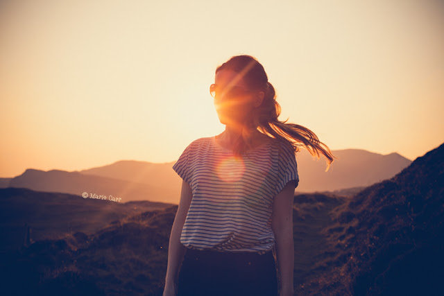 Portrait of woman with long hair against the sun setting at golden hour