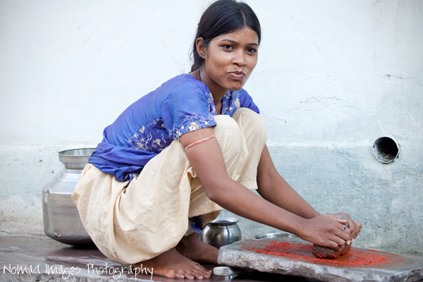 indian girl making chili paste on the street