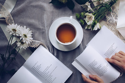 Open books, cup of tea and sprig of flowers as woman plan's her wedding.