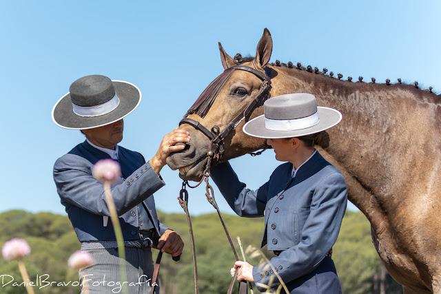 Matrimonio de jinetes acarician a un caballo y éste parece sonreír