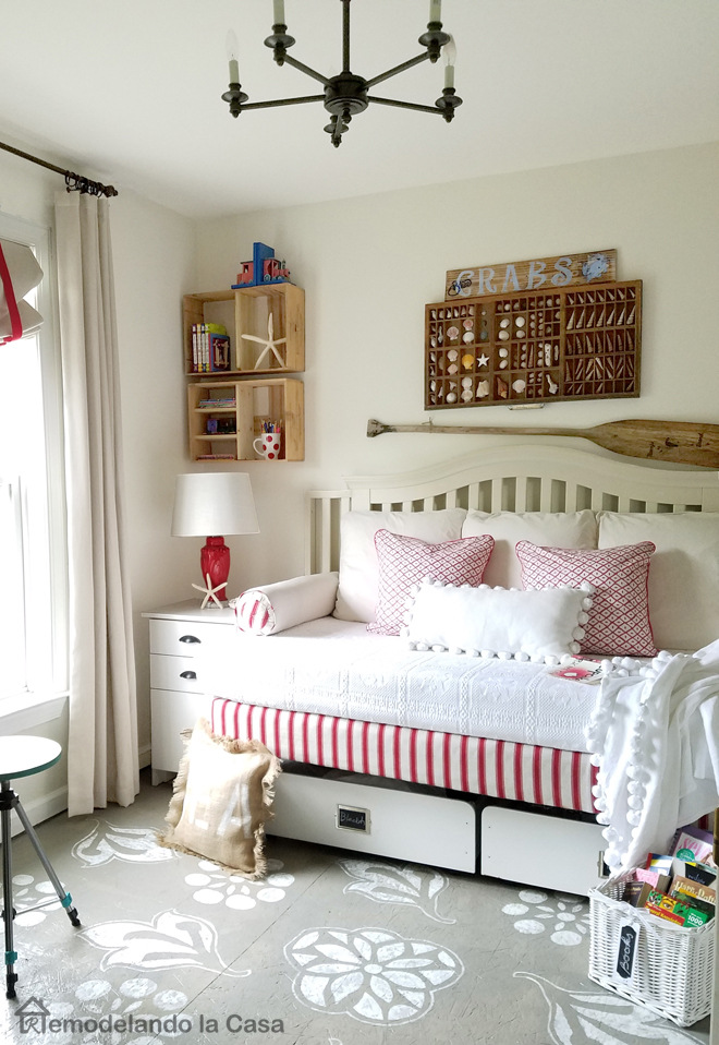 painted designs on the floor, round mirror, daybed out of spring box, wine crates wall storage