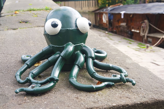 a dark green metal octopus sculpture sits on the wall by the canal