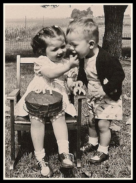 - Vintage photo cute little girl shares frosting from a birthday cake wihth a little boy. c1950s