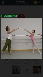 В зале тренер проводит занятие с учениками и показывает позицию из балета