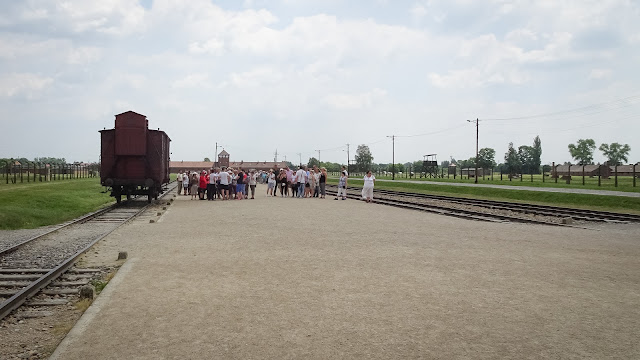 Tourists climbing around trains in Auschwitz
