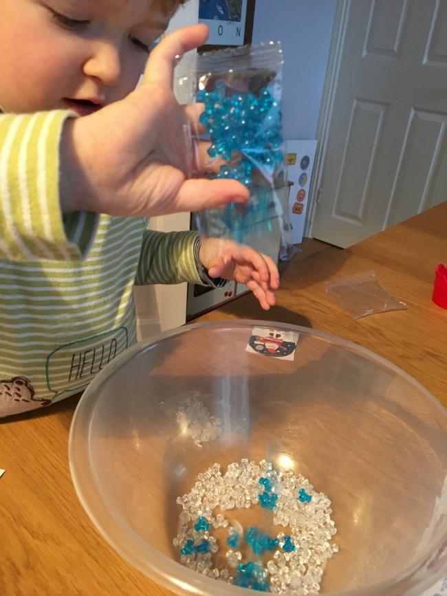 toucanBox-Subscription-Box-review-toddler-emptying-beads-into-a-bowl