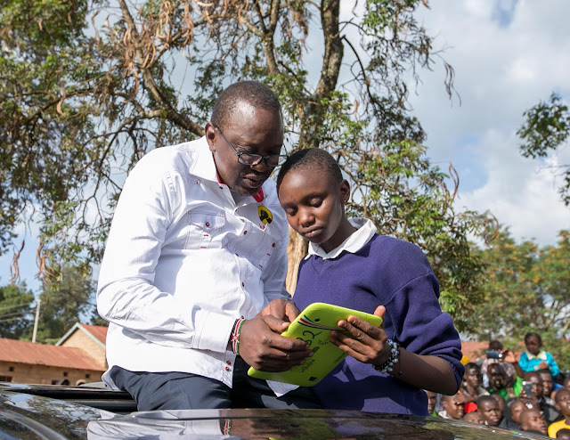 President Kenyatta with a primary school child in Kiambu. PHOTO | Courtesy PSCU