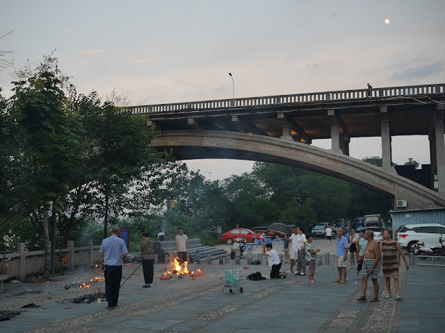 people burning ghost money near the Donghe Bridge in Ganzhou