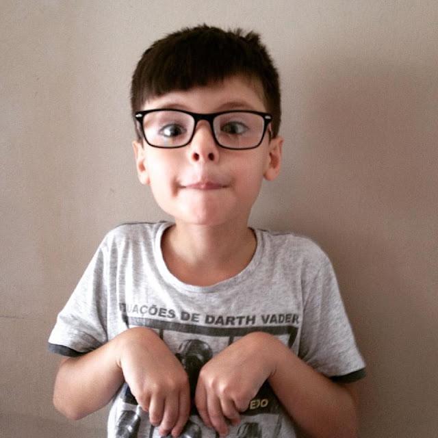 Foto do Miguel imitando coelho com seu novo óculos.
