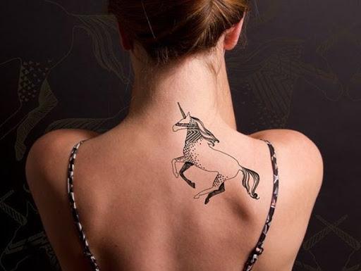 Vai tribal sobre o unicornio tatuagens