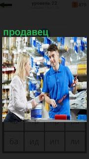 в магазине мужчина продавец показывает и рассказывает о товаре
