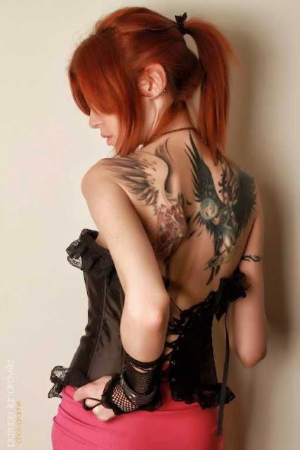 Foto de una preciosa mujer peliroja con tatuaje de angeles en la espalda