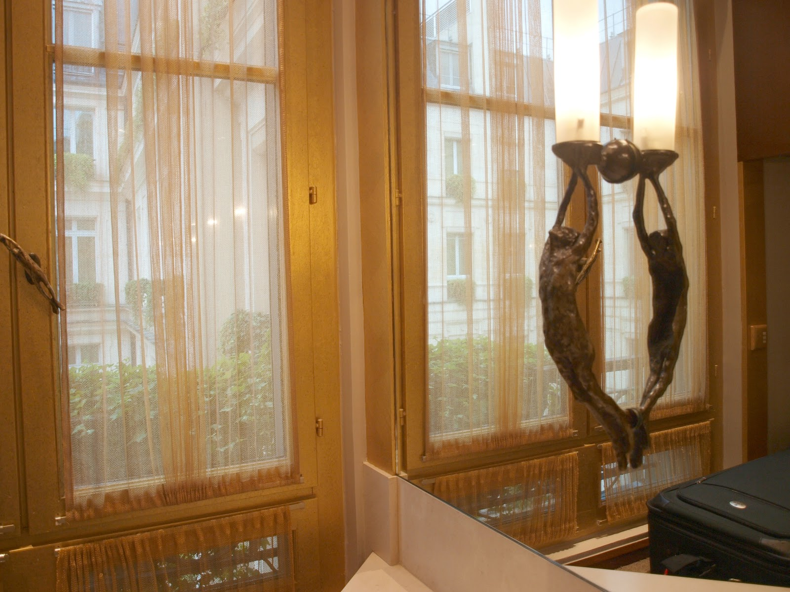 Silk curtains, French windows, and bronze scujpture in elegant bathroom of Park Hyatt Paris Vendome - by Hello Lovely