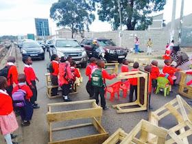 KENYA PALAVER: Primary school children block road with desks after their school was demolished