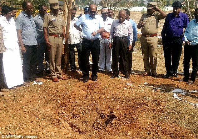Indian authorities inspect the site of a suspected meteorite landing on February 7, 2016 in an impact that killed a bus driver and injured three others on February 6. If proven, it would be the first such death in recorded history. The impact of the object left a large crater in the ground and shattered window panes in a nearby building, killing the driver who was walking past. Credit: AFP/Getty Images