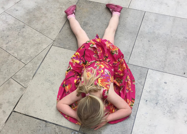 A young girl lying on the floor in a shopping centre having a tantrum