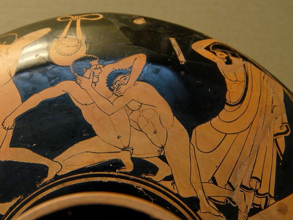 Σκηνή από παγκράτιο: ο αγωνιστής στα δεξιά προσπαθεί να τρυπήσει το μάτι του αντιπάλου του, ο κριτής είναι έτοιμος να τον αποκλίσει για αυτό το φάουλ. Λεπτομέρεια από αττική ερυθρόμορφη κύλικα.