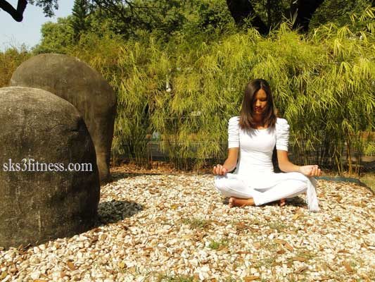 A girl meditating in Varun mudra / hand gesture on ground of park in sunlight