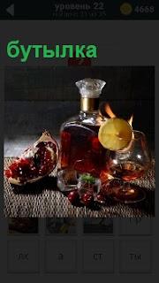 На столе стоит бутылка со спиртными напитками и рядом разрезанный гранат и стакан с лимоном наполовину заполненный вином