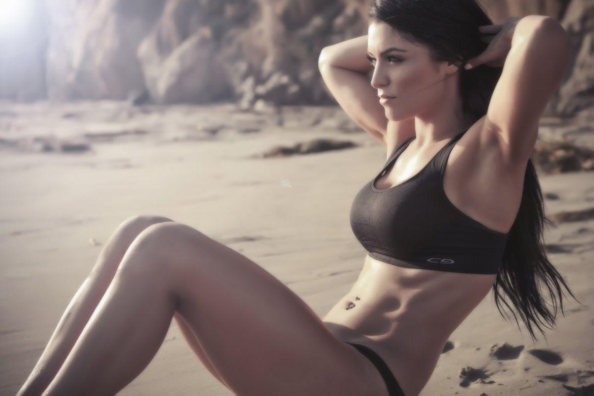 Mujer haciendo abdominales en la playa. | Rane Forti
