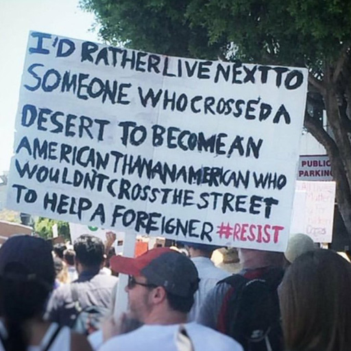 "A pro-immigration supporter with a sign which reads, ""I'd rather live next to someone who crossed a desert to become an American than an American who wouldn't cross the street to help a foreigner #resist"""