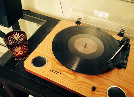 image of a record player, sitting on a sideboard, with a glass of Scotch sitting beside it