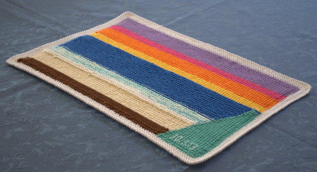 A single placemate complete. A white border contains horizontal stripes of (bottom to top) brown, sand, white, variegated aqua/white, blue, yellow, orange, pink and purple with a block of green on the right hand side. A date is embroidered on the green fabric in the bottom right hand corner.