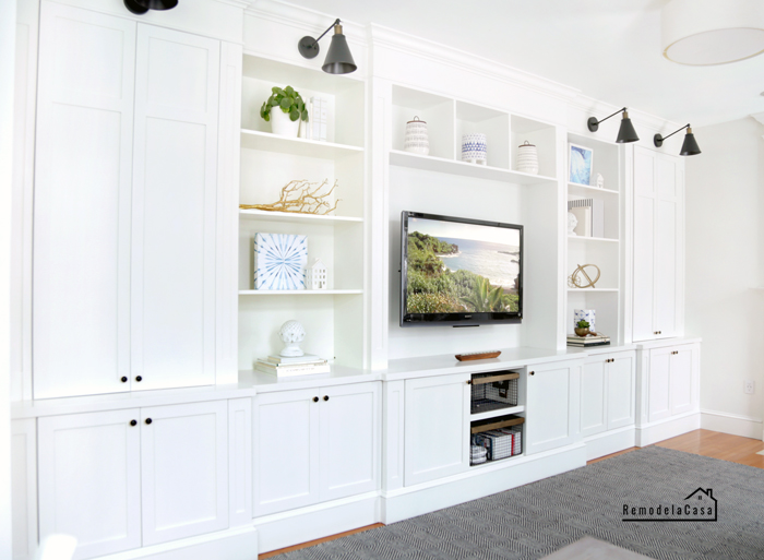 An entire wall of shelves holding the tv in the center of the family room #fastcabinetdoors