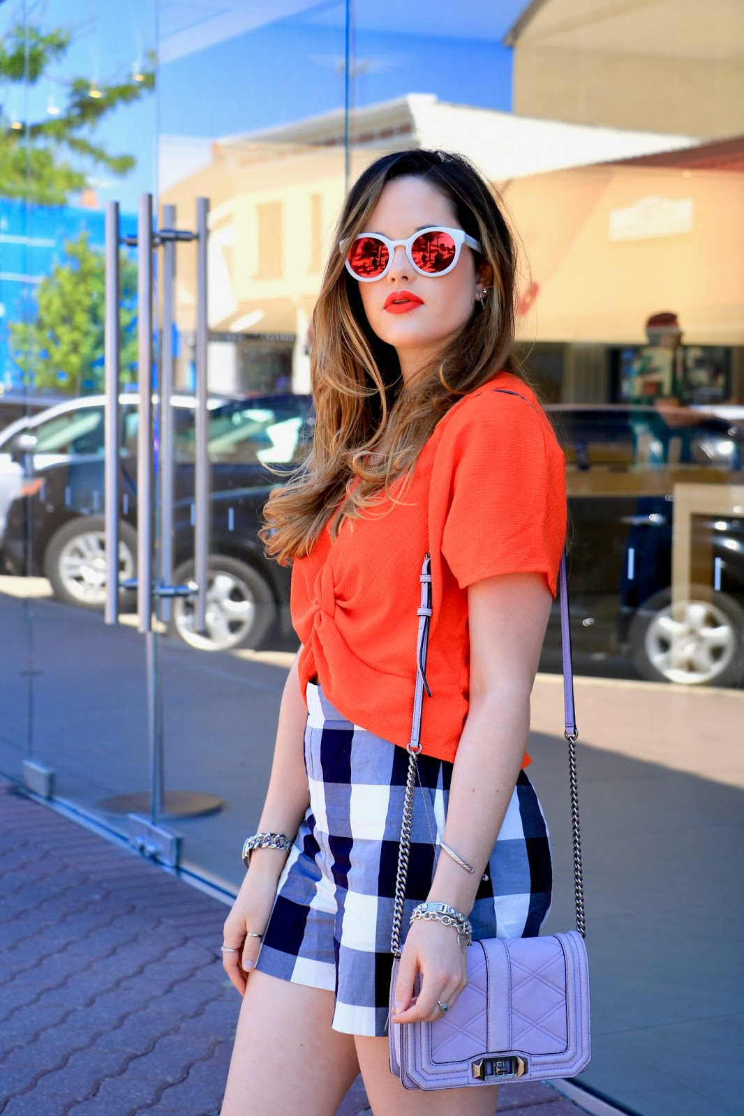 Nyc fashion blogger of Kat's Fashion Fix, Kathleen Harper, wearing orange twist top and plaid shorts