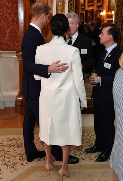 Meghan Markle wore Amanda Wakeley cream sculpted tailoring crombie coat, The Duchess is wearing a midi dress with ruffle detail