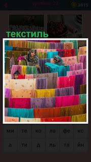 на улице на веревках развешан цветной текстиль