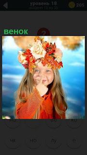 Девочка на фоне неба с венком на голове и палец приложила к носу