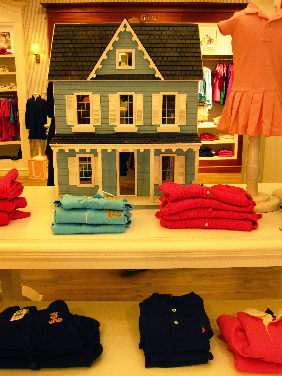 Dolls' house displayed in a children's wear department.