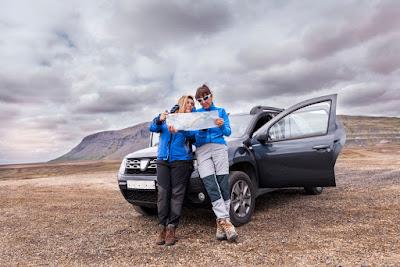 Pareja verificando el mapa de carreteras para conducir por Islandia