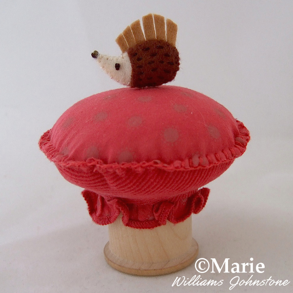 Handmade cotton reel spool pincushion with a hedgehog pin and toadstool design