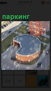 Необычной формы паркинг находится рядом с жилыми домами, куда въезжают автомобили на стоянку