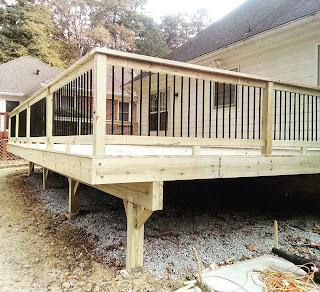 Cantilevered backyard deck with round black balusters