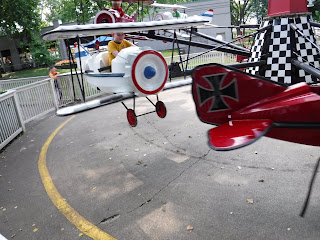boy riding the Red Baron airplane ride at Adventureland in Altoona, Iowa