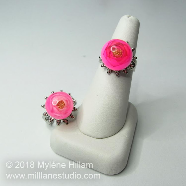 Two UV Resin rose rings, one light pink and one dark pink, displayed on a white ring cone.