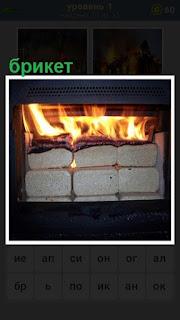 Горит печка, а в ней сложены брикеты в качестве топлива