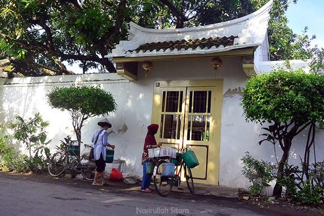 Para penjual sayuran menunggu pembeli di depan rumah warga